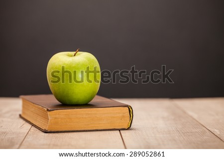 apple and book on wooden table - stock photo