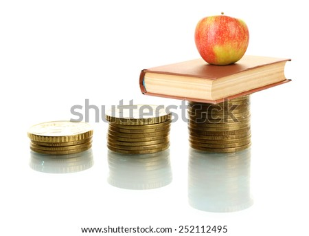 Apple and book standing on stack of coins isolated on white - stock photo