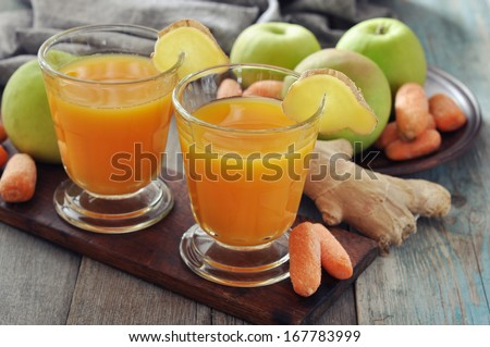 Apple and carrot juice in glass with ginger,  fresh vegetables and fruits on wooden background - stock photo