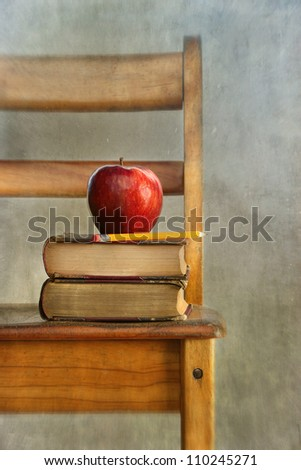 Apple and old books on school chair with vintage feel - stock photo