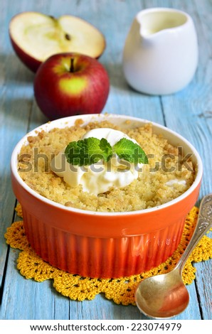Apple and pear crumble in orange container. - stock photo