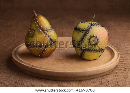 apple and pear manipulated fruit with nails holding it together genetic modification gmo concept - stock photo