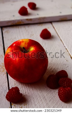 Apple and raspberries on rustic wooden table, selective focus - stock photo