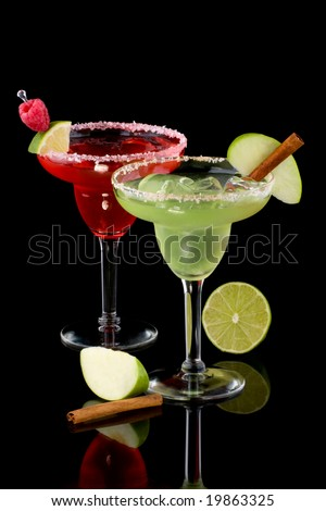 Apple and Raspberry margaritas in chilled glass over black background on reflection surface, garnished slice of green apple, fresh raspberries, slice of lime and cinnamon stick.