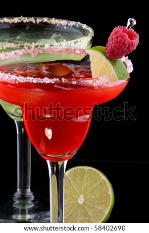 Apple and Raspberry margaritas in chilled glass over black background on reflection surface, garnished slice of green apple, fresh raspberries, slice of lime and cinnamon stick. - stock photo