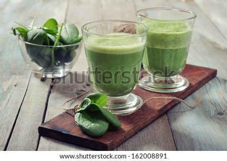 Apple  and spinach smoothie in glass on a wooden background - stock photo