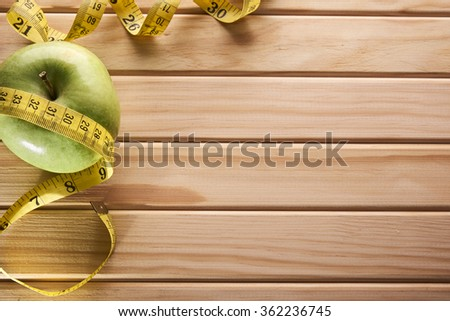 Apple and tape measure on wooden floor. Concept health, diet, nutrition. Horizontal composition. Top view - stock photo