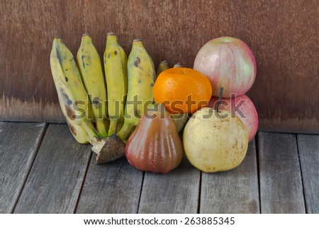 apple, bananas, orange and rose apple on gray old wooden table - stock photo