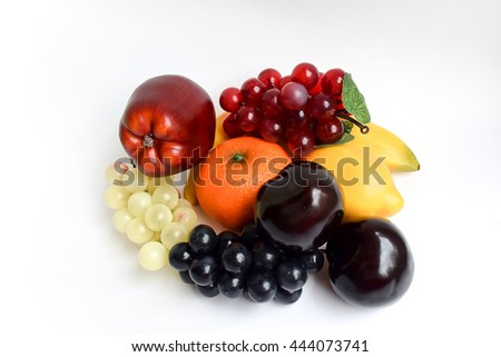 Apple, black grapes, red grapes, white grapes, tangerine, lemon, banana and two plums on a white background - stock photo
