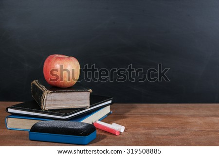 Apple, books and chalks on the wooden table with blackboard background.