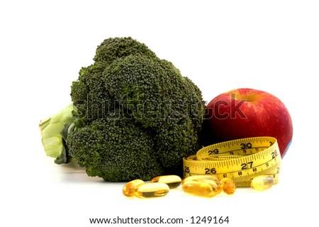 Apple, broccoli,fish oil caplets and measure tape - stock photo