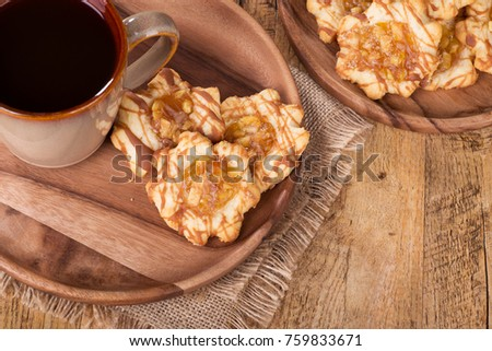 Apple caramel cookies on a wooden plate with cup of coffee