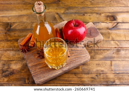 Apple cider in glass bottle with cinnamon sticks and fresh apples on cutting board, on wooden background - stock photo