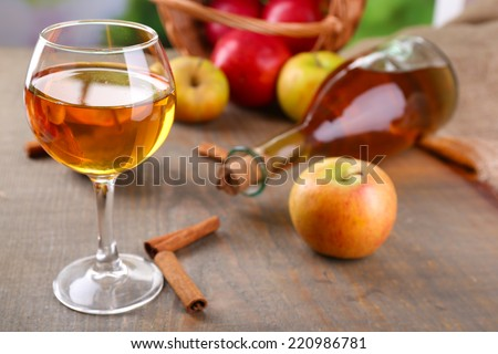 Apple cider in wine glass and bottle, with cinnamon sticks and fresh apples on wooden background - stock photo