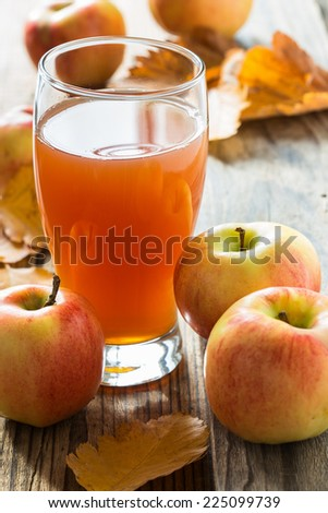 Apple cider ready to drink and ripe organic apples on wooden background with autumn leaves - stock photo