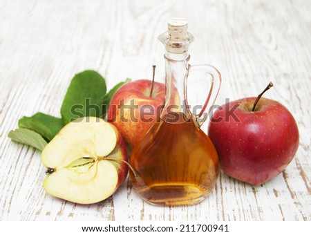 Apple cider vinegar and fresh apple on a wooden background - stock photo