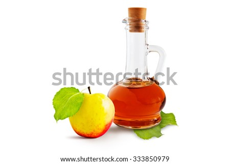 Apple cider vinegar cruet and ripe apples with green leaves on a white background - stock photo