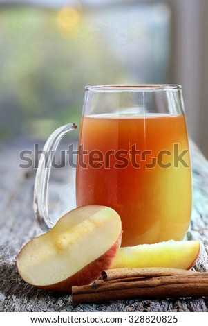 Apple cider with cinnamon sticks and fresh apples on weather worn table top - stock photo