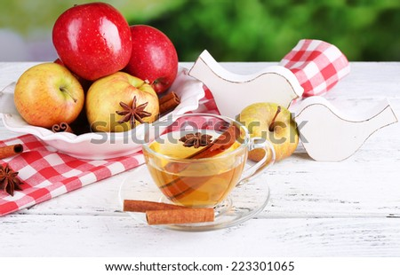 Apple cider with cinnamon sticks and fresh apples on wooden table, on bright background