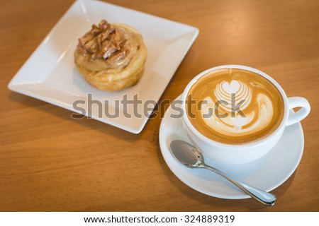 Apple cinnamon roll served with cappuccino coffee on the table at restaurant. - stock photo