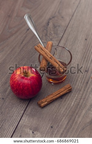 Apple, cinnamon sticks, and a glass with honey on a wooden table