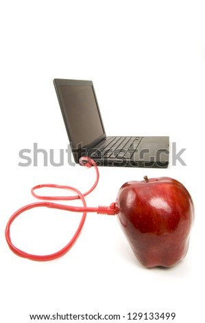 Apple connected with a cable to a laptop isolated on white background - stock photo