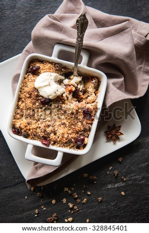 Apple crumble cake with dried fruit on wooden background - stock photo