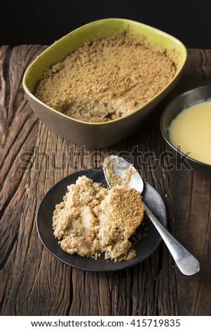 Apple Crumble Dessert. Homemade Apple Crumble pudding sitting on a rustic wooden table. - stock photo