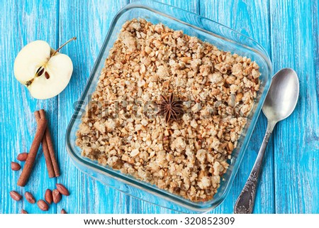 Apple crumble dessert on wooden background with apples, cinnamon and anise - stock photo