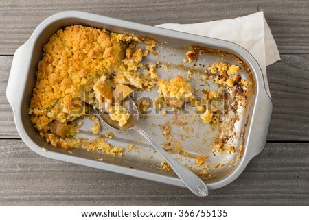 Apple crumble in cake pan with spoon on wooden table - stock photo