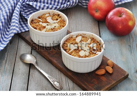 Apple crumble in ceramic molds with fresh apples on wooden background - stock photo
