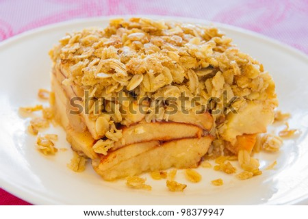 Apple crumble portion in a white plate. Shallow depth of field.
