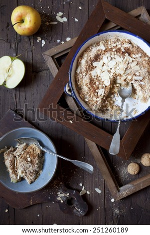 apple crumble with almonds on rustic table with wood frames and two spoons - stock photo