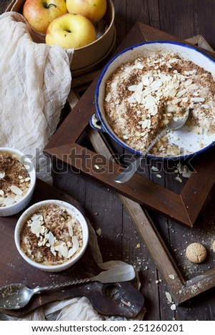 apple crumble with almonds on rustic table with wood frames, whole apples and cloth - stock photo
