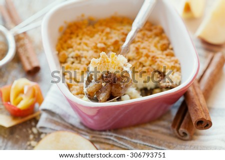 Apple crumble with cinnamon on rustic wooden table - stock photo