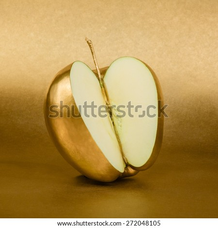 Apple cut with golden peel on gold background - stock photo