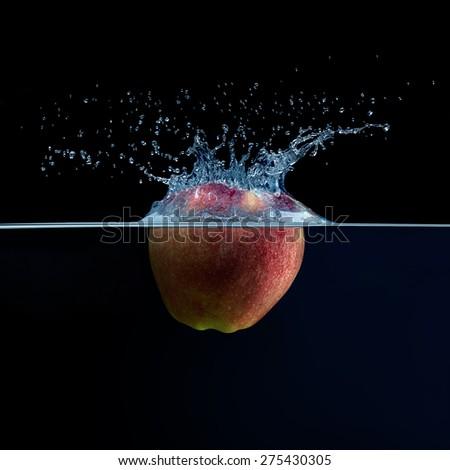 Apple falls into the water. Water splash. Fruit, spray, splash, - stock photo
