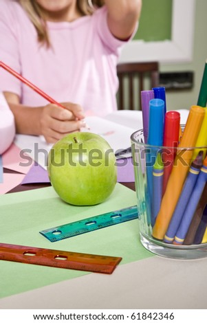 Apple for the teacher on student desk in classroom - stock photo