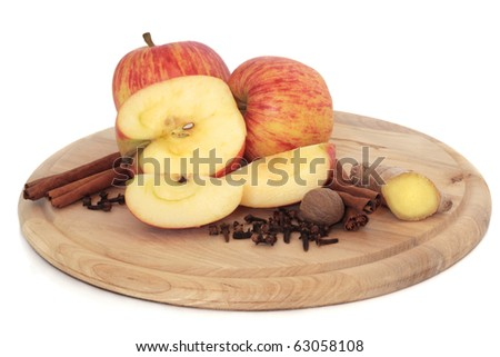 Apple fruit with cinnamon sticks, ginger root, cloves and nutmeg spice on a wooden board, isolated over white background. Gala variety. - stock photo