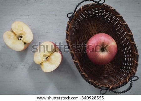Apple halves of apples in the basket. On a gray wooden desk , top view - stock photo