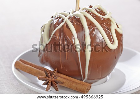 Apple in chocolate on a white plate with cinnamon and anise star