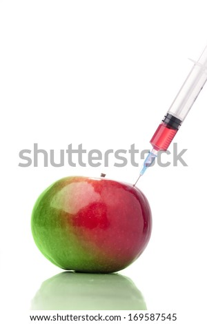 Apple in two colors with a syringe. Concept for genetically modified foods. - stock photo
