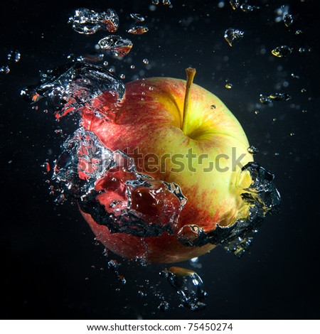 Apple is under water in a stream of air bubbles on a black background - stock photo