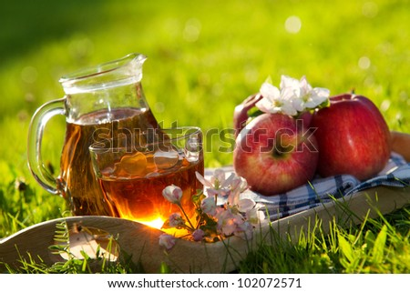 Apple juice and apples on wooden table on fresh green  background - stock photo