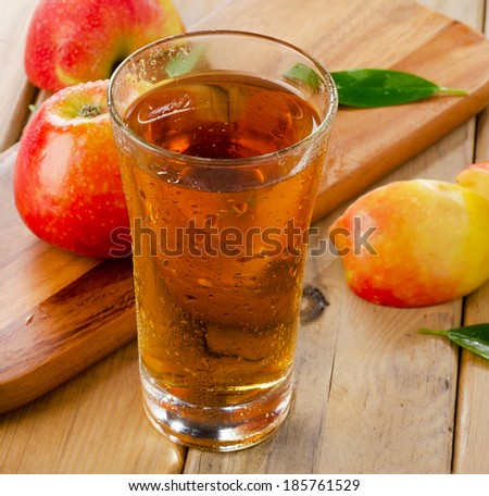 Apple juice and apples on wooden table. Selective focus - stock photo