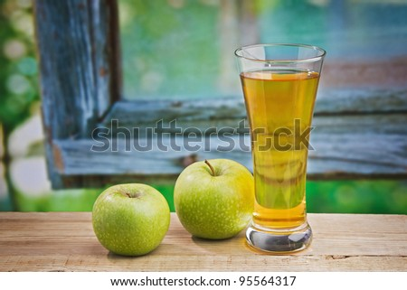 Apple juice in a glass on a table with apples - stock photo
