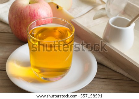 Apple juice in glass on wooden table.
