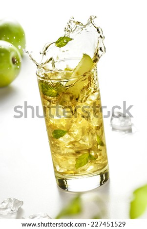 Apple juice splashing in glass on white background