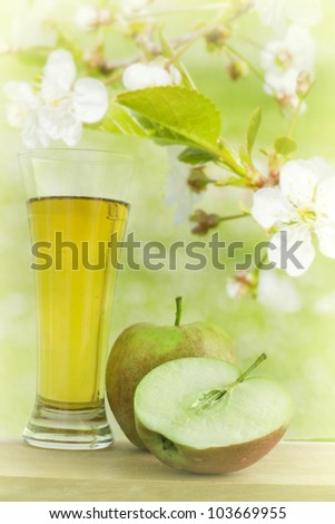 apple juice with apple in the colorful garden with flowers ,abstract background