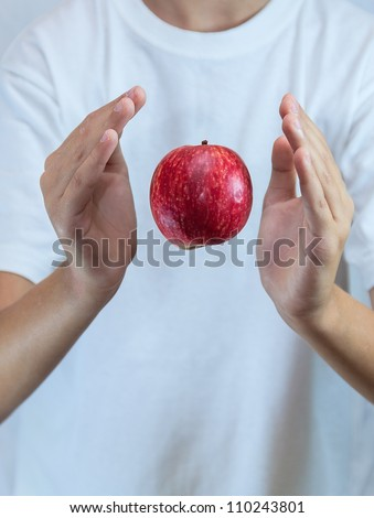 apple levitates above the hands  in the air on a white background